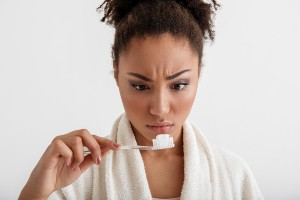Woman Looking at Toothpaste